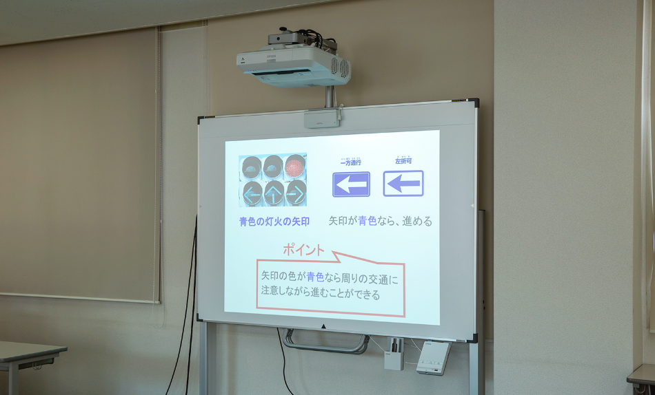 大型スクリーンに講義内容が映し出されている写真