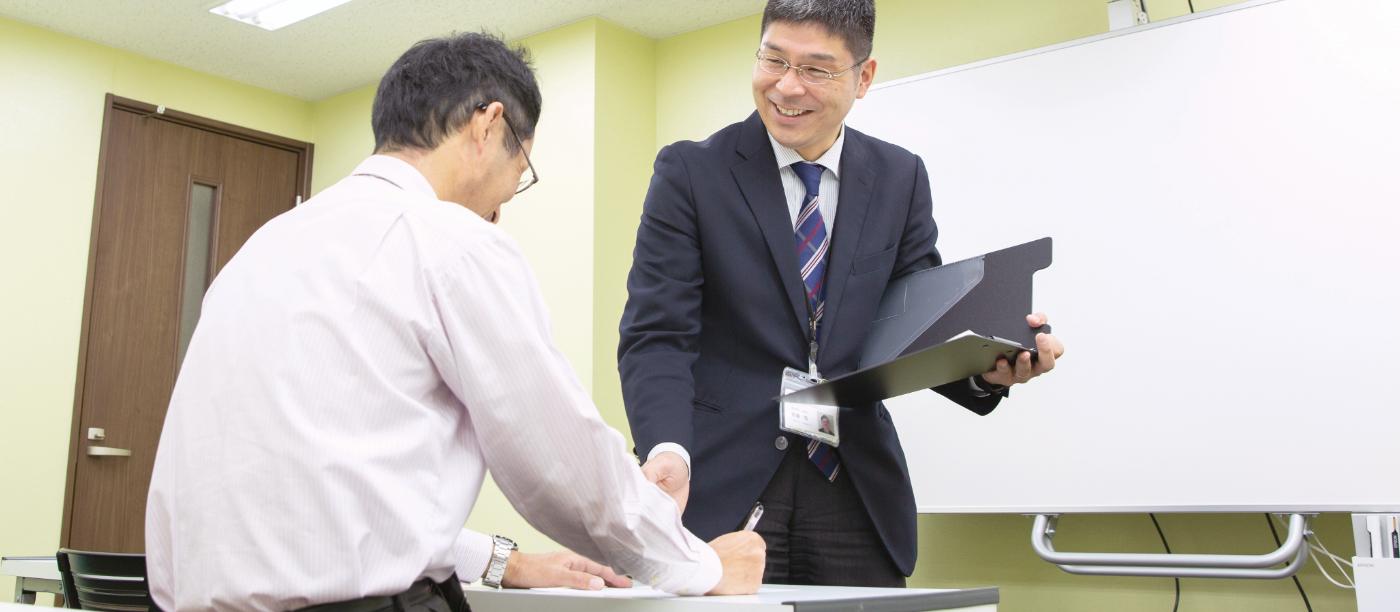 企業講習の学科講習を受ける教習生とインストラクターの写真