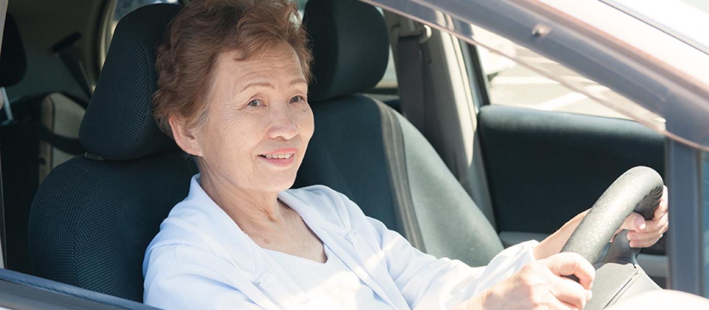 教習車に乗って講習を受ける女性の写真